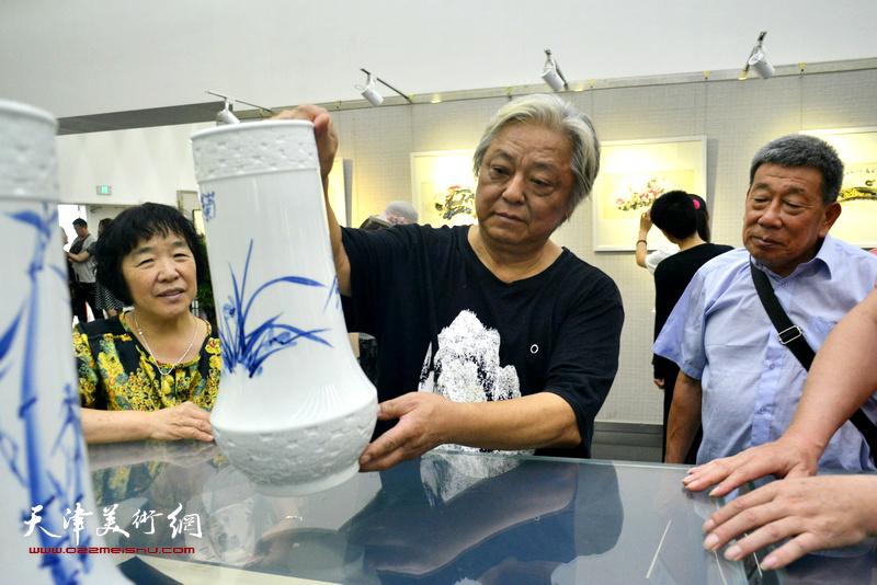 鲁平在画展现场向观众介绍他的青花瓷作品。