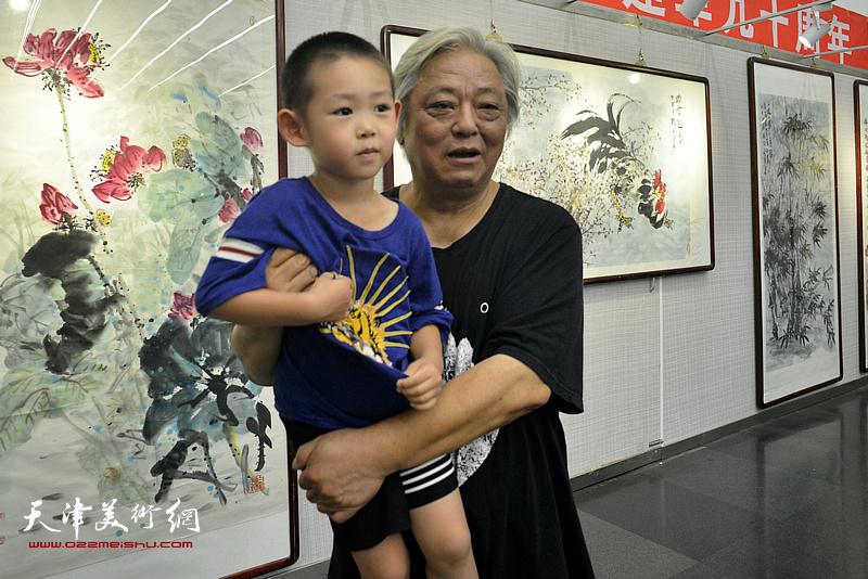 鲁平与小画家在画展现场。