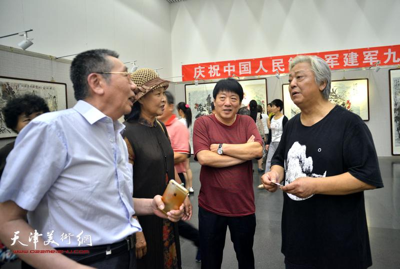 鲁平与高原春、曹剑英、单国钧在画展现场交流。