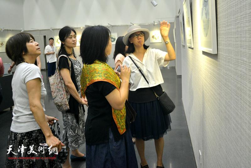 瀛樱在画展现场向日本朋友介绍中国书画艺术。