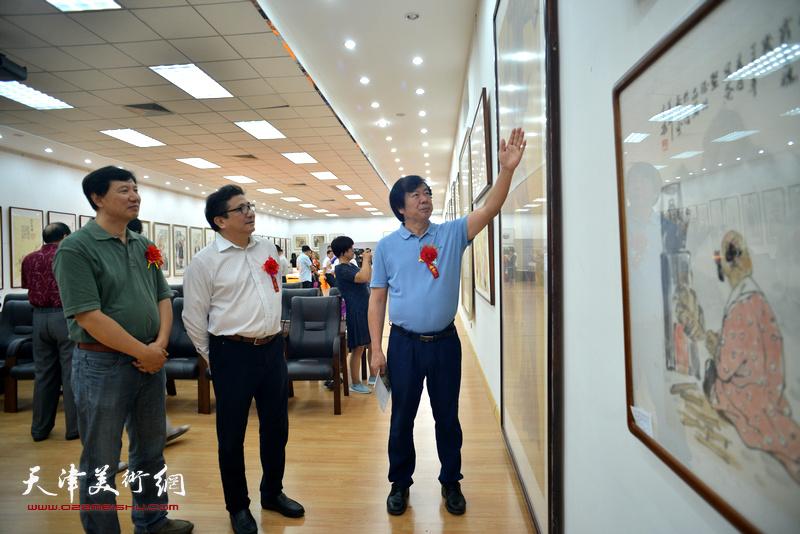 商移山、史振岭、张福有在画展现场观赏作品。
