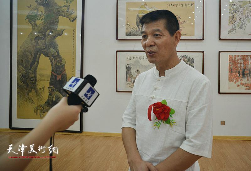 范扬在画展现场接受媒体采访。