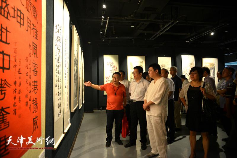 张平、曲伟、吕大江、李博隽在观赏展出的作品。