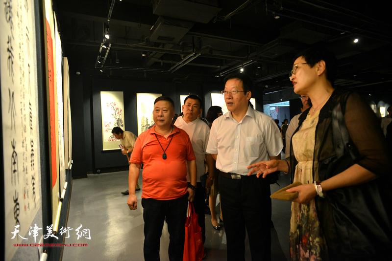 郑少英向张平介绍展出的作品。