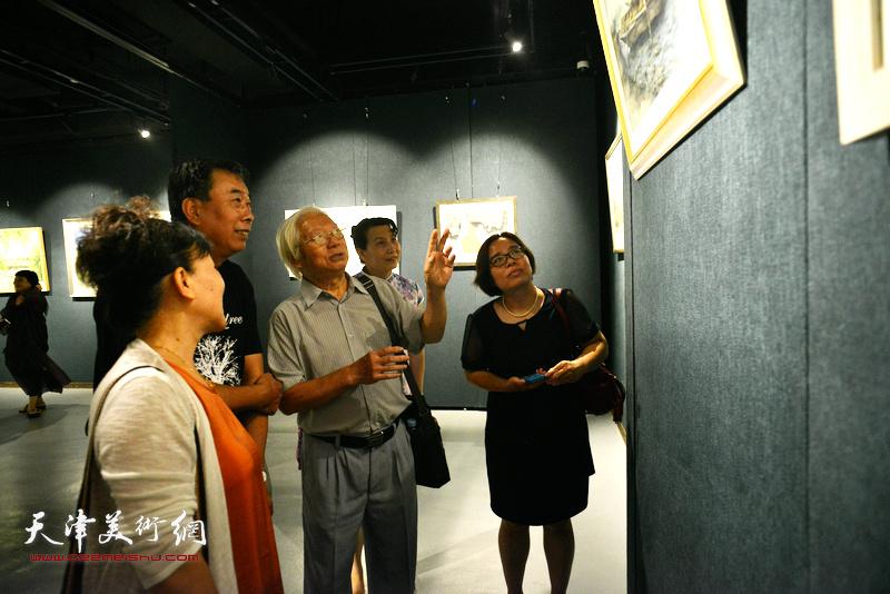 贺建国在画展现场向观众讲解作品。