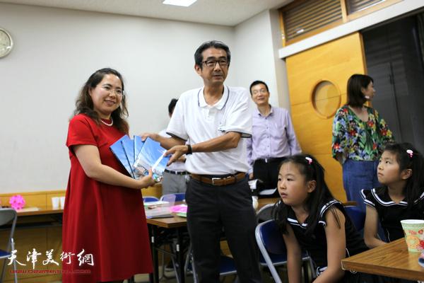 王莹向日本神奈川县伊势原市教育部部长龟田赠送书籍。