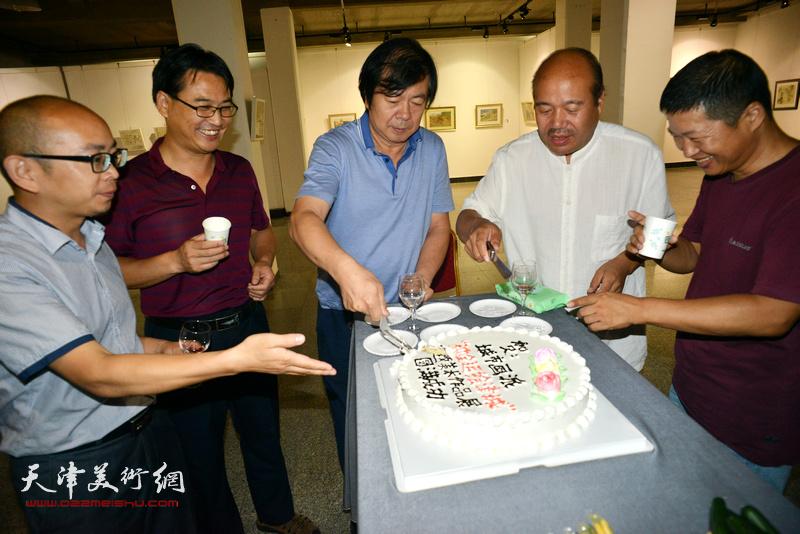 史振岭、孟庆占为画展切开揭幕蛋糕。