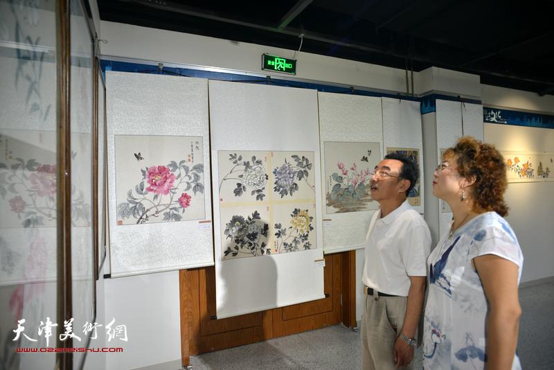柳春水与张春蕾在观赏展出的作品。