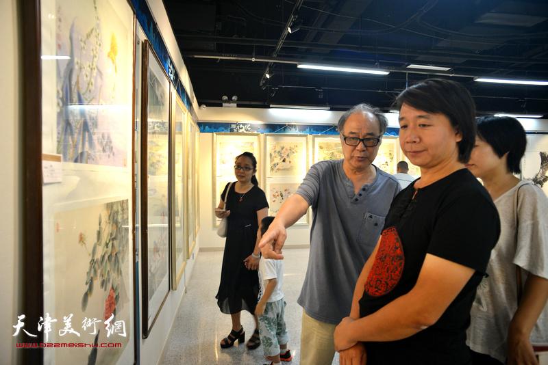 郭书仁与范宁在观赏展出的作品。