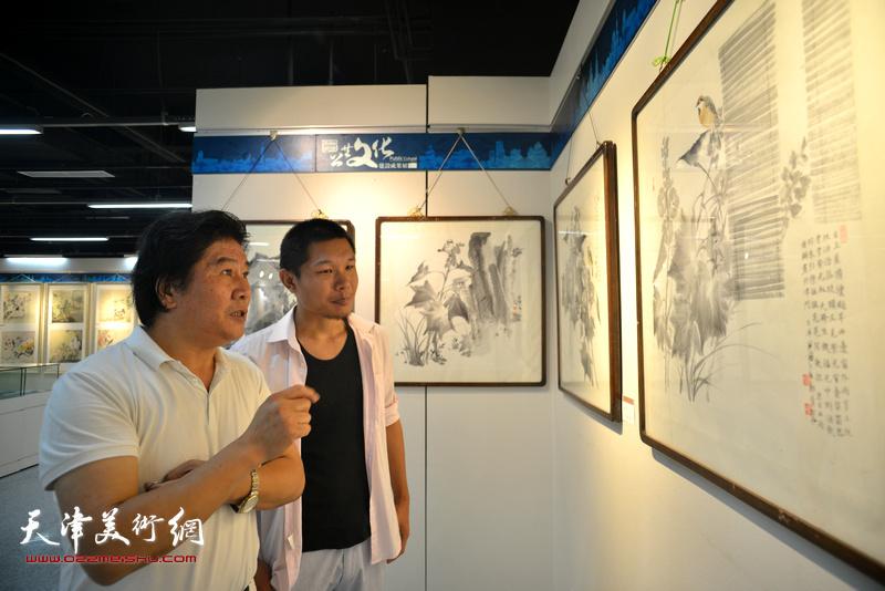 高学年与郑伟在观赏展出的作品。