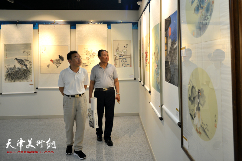 刘传光、柳春水在观赏展出的作品。