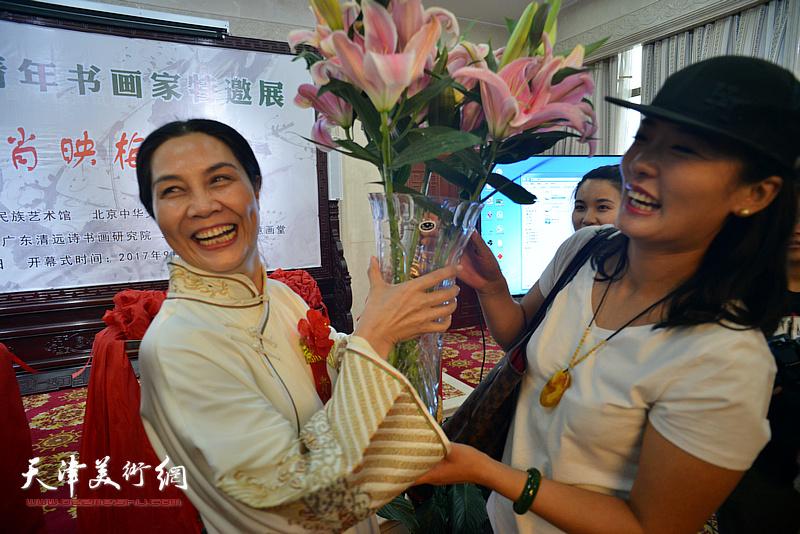 来宾为肖映梅献花。