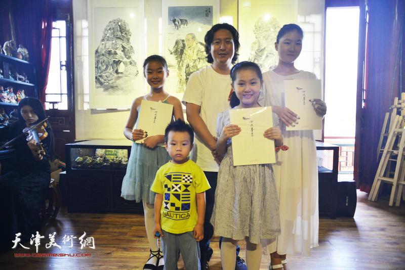 梁健与少年古筝乐手高浩荣、李梓源、韩孟辰在画展现场。