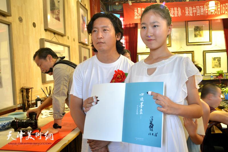 梁健与少年古筝乐手高浩荣在画展现场。