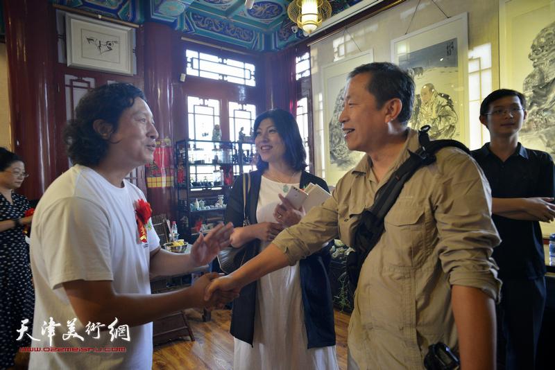 梁健与来宾在画展现场。