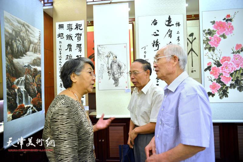 李润兰与张俊屹、郭文伟在画展现场交流。
