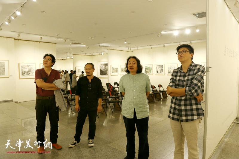 贾广健、晏平、李旭飞在观赏展出的作品。