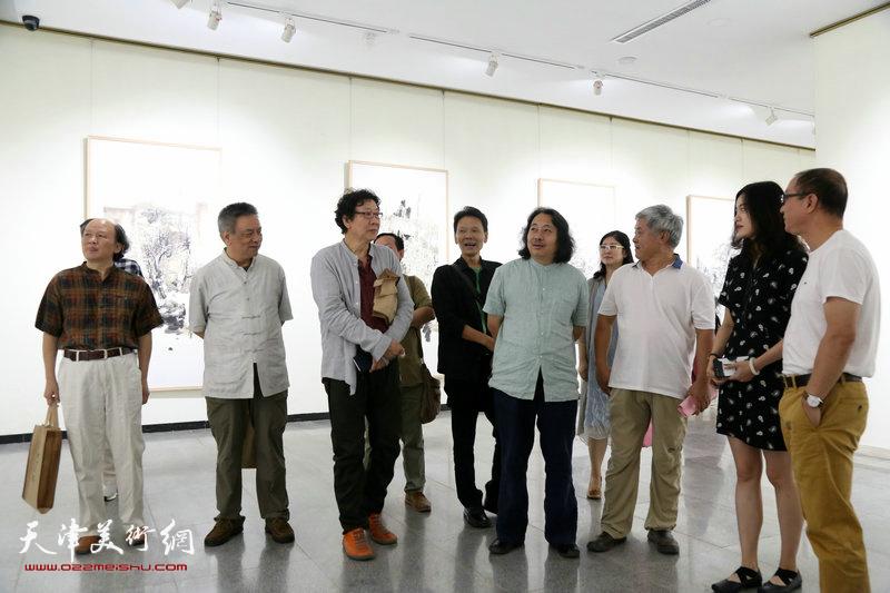 贾广健、晏平等参展画家在观赏展出的作品。