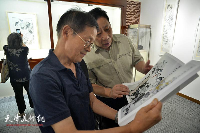 尚金声、杨利民在画展现场阅览出版的画集。
