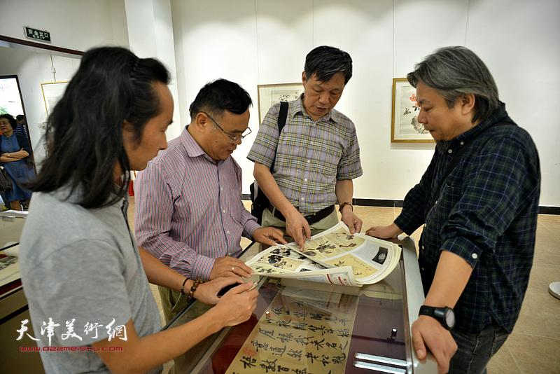孟庆祥、李泓伯、田正宪、安士胜在画展现场观看作品。