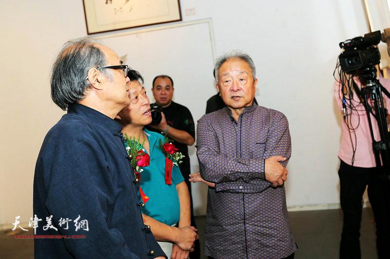 李军陪同况瑞峰、郭书仁观赏展出的作品。