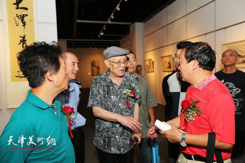孙长康与沈德强、李军在书画展现场交流。