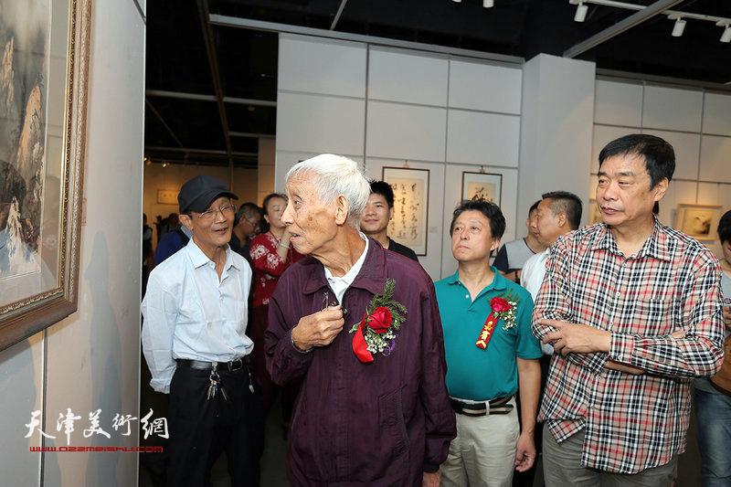 李军陪同刘光启、姜维群观赏展出的作品。