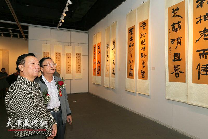 陈启智、张建华观赏展出的作品。