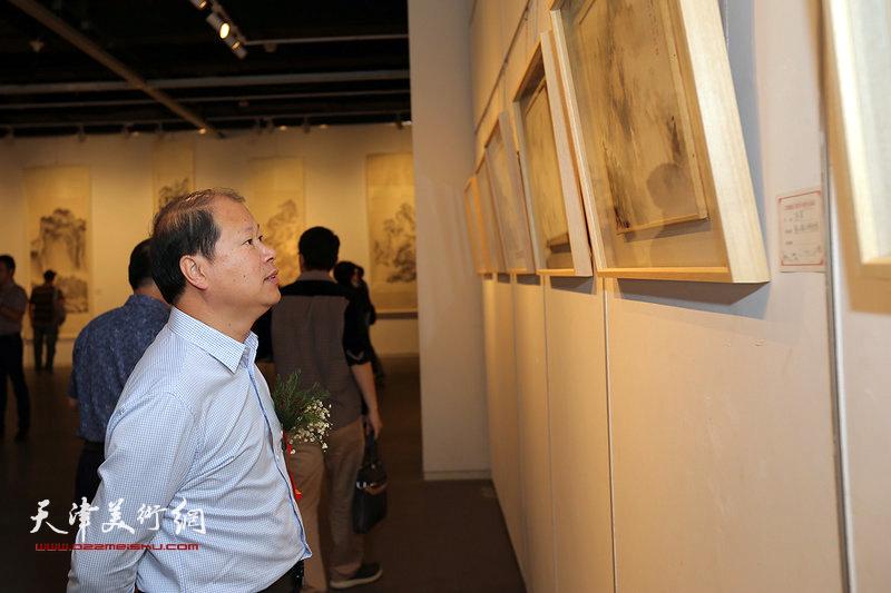 李锋在观赏展出的作品。