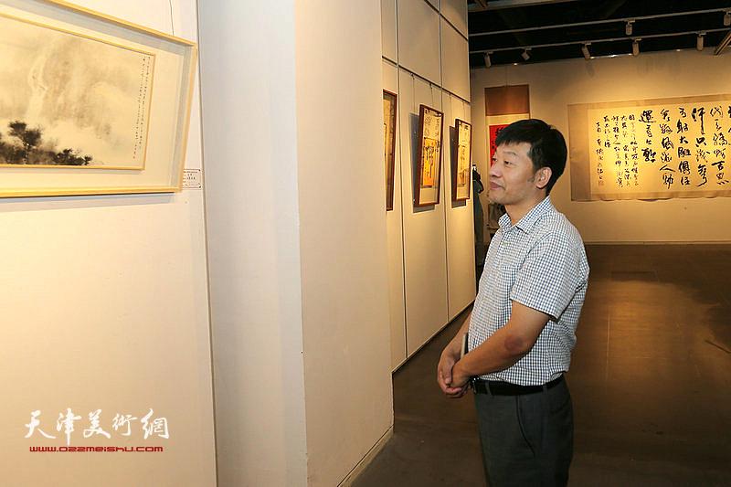 杨占良在观赏展出的作品。