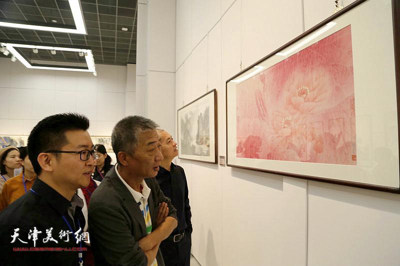天津美术学院院长邓国源观摩展出的画作。
