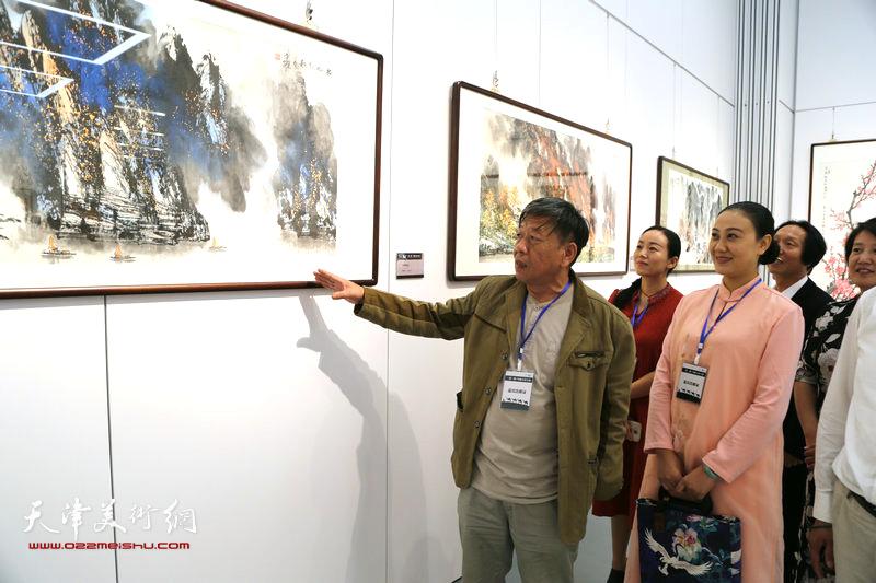 著名画家李京跃向观者讲解自己绘画作品《杨帆起航》。