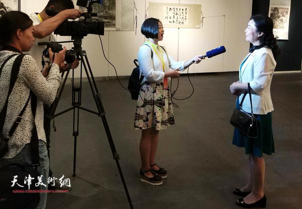 天津市侨联副主席、党组副书记陈钟林在画展现场接受媒体采访。