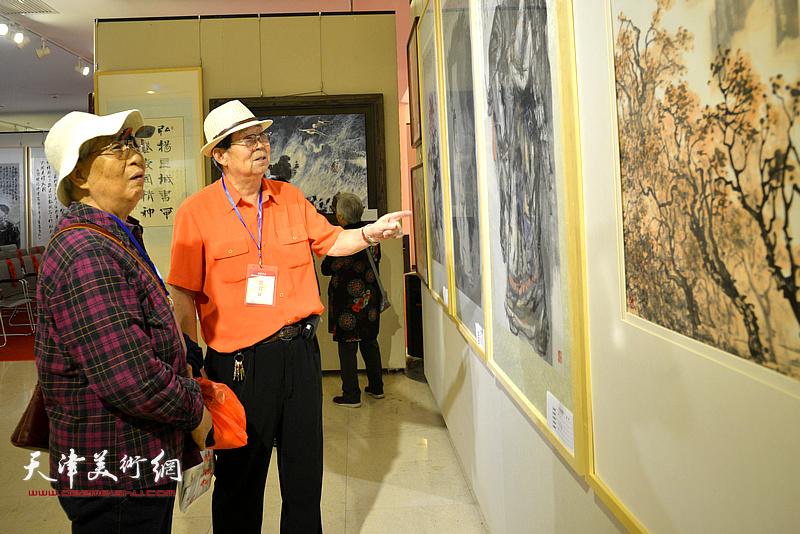 郭永元夫妇在观赏展出的作品。