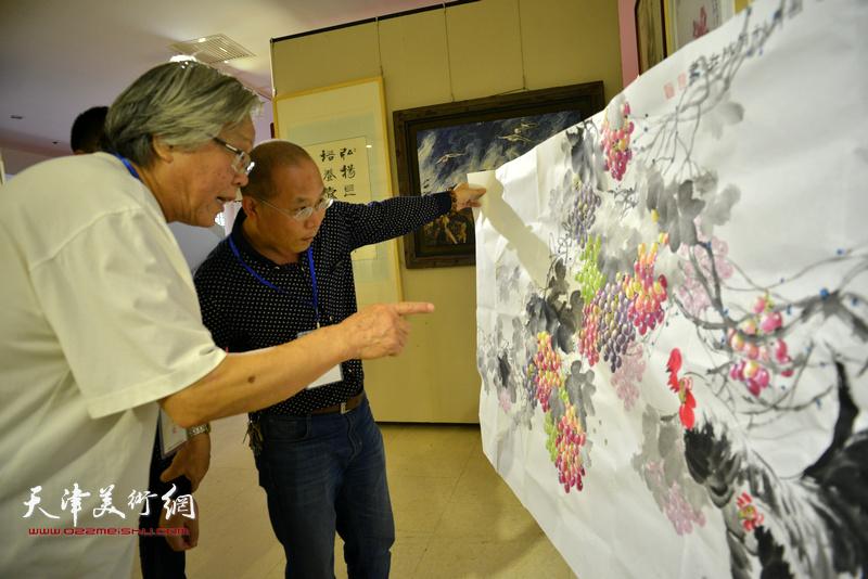 陈冬至在画展现场为书画爱好者评点作品。