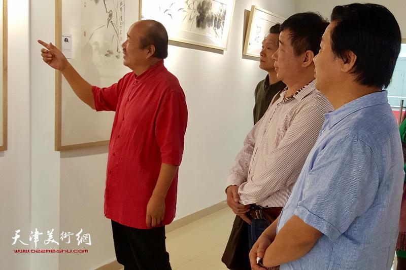 孟庆占与来宾观赏展出的展品。
