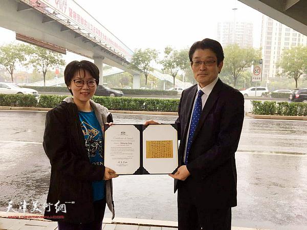 日本国际美术家协会会长金原先生在南翠屏天桥底下把奖状颁发给唐曼清。
