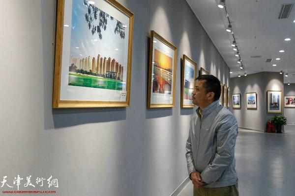 天津市摄影家协会秘书长包静在影展现场观展