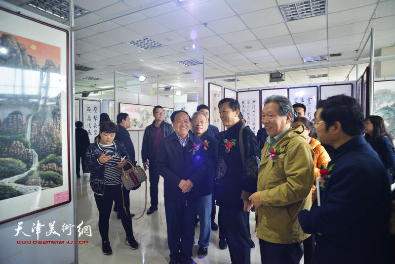 霍然、王金厚陪同周国江、郎岗峰观赏作品。