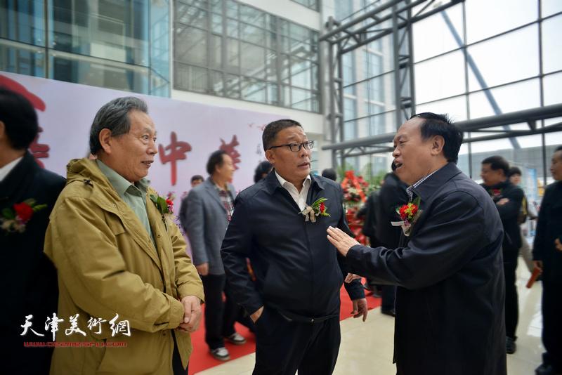 霍然与戎阳、周国江在画展现场交流。