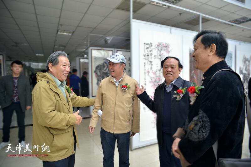 霍然与周国江、赵庆钢、郎岗峰在画展现场交流。