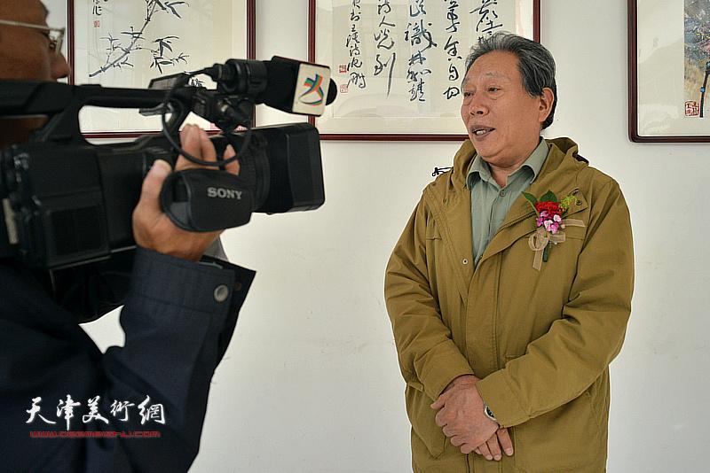 霍然在画展现场接受媒体采访。