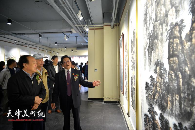 曲学真陪同周国江、赵庆钢观赏展出的作品。