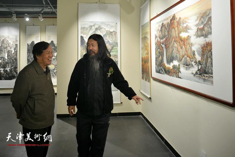 蒋峰、梁旭华在观赏展出的作品。