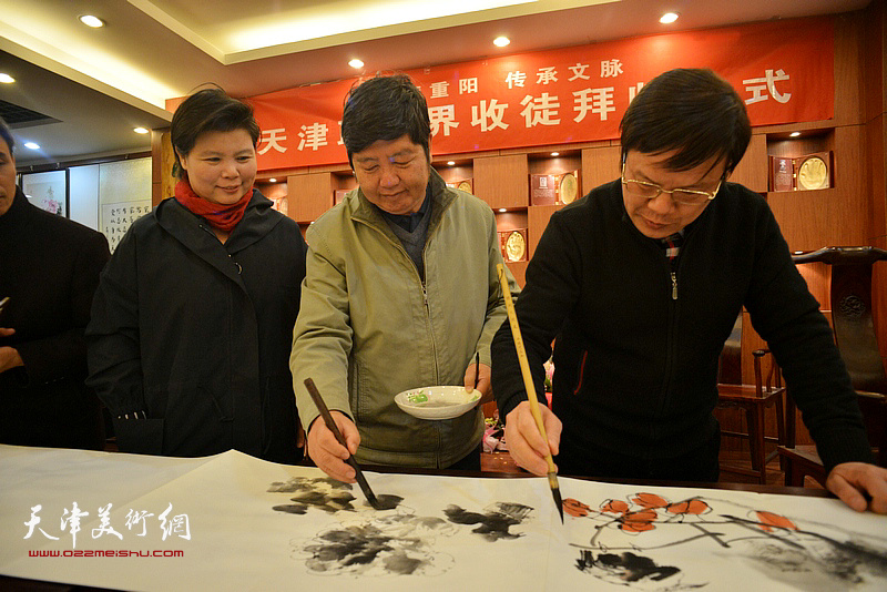 书画家现场挥毫泼墨喜庆十九大胜利召开。图为刘红、王惠民、李根友。