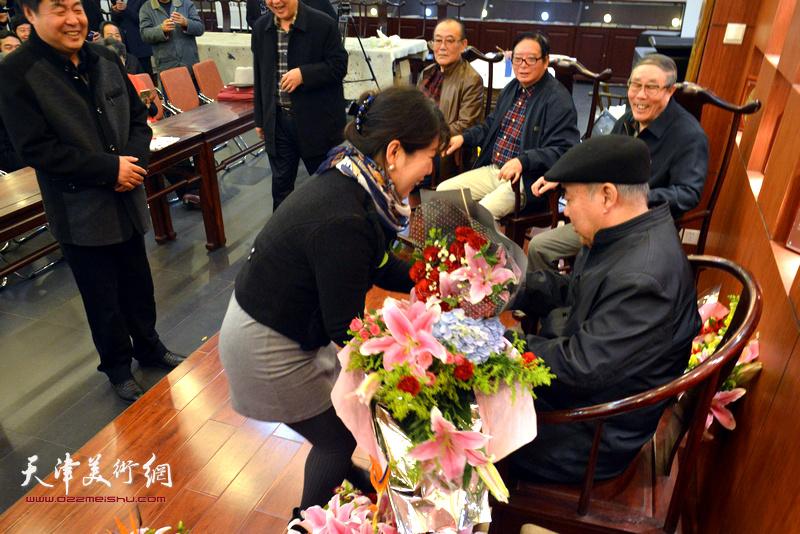 新弟子陈艳梅向师傅王焕墉献花。