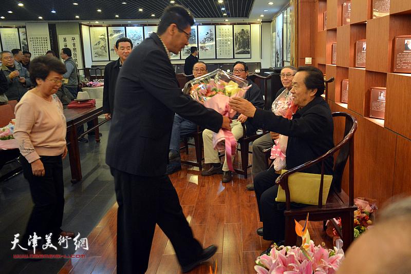 于勇、贺美华向师傅王全聚献花。