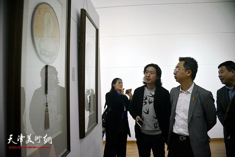 梁健向刘桓等介绍展出的作品。