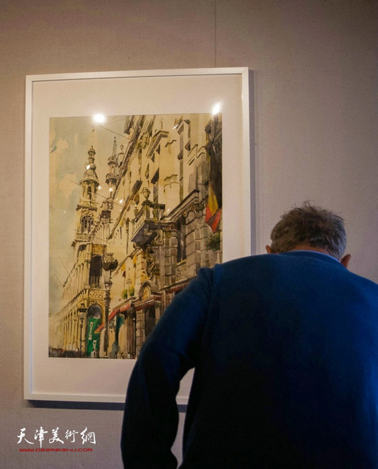 在展出的纪伟作品前,一位观众察看作者简介。