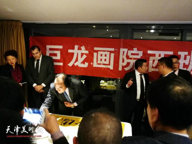 天津书画家在画展现场演示中国书画艺术。